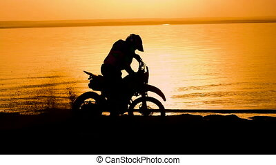 Off-road motorbike extreme cornering. Motorcyclist at sunset near the river. Extreme motocross bike, dirt from under the wheels.