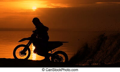 Off-road motorbike extreme cornering. Motorcyclist at sunset...
