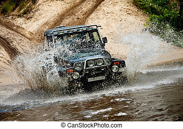 Off-road. The vehicle splashing water from the river