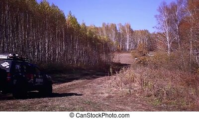 Off road SUV vehicle running in autumn forest on road