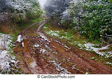 Off-road track   in the autumn forest with snow