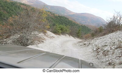off-road vehicle driving on rocky dirt road down the mountain slope
