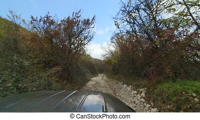 Off-road vehicle driving on stony mountain track to Mangup...