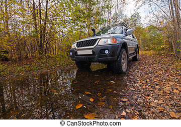 Off road vehicle in autumn forest