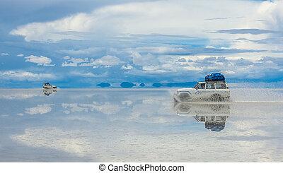 Off-road vehicles driving in Salar de Uyuni, Bolivia, the world's largest salt flat