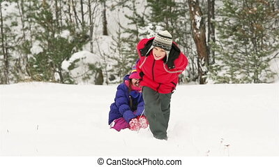 Off The Sled - Children playing outdoors on a winter day,...