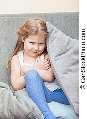 Offended Caucasian girl hiding behind a pillow on the couch. Folded her arms