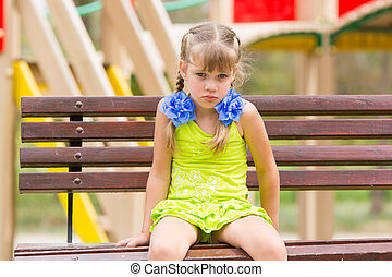 Offended five year old girl sitting on a bench at the playground
