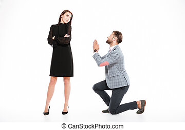 Offended young loving couple standing isolated