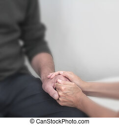 Cropped image focusing on therapist holding client's hand offering comfort with a soft blur effect on everything except the hands.