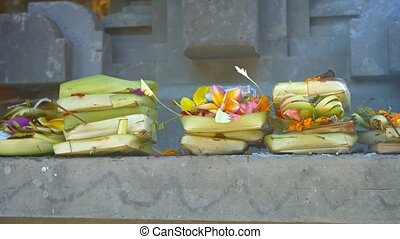 Offerings of money, flowers and incense to Hindu gods, presented on a long, cement altar at Tirta Empul Temple in Bali, Indonesia. Video UltraHD