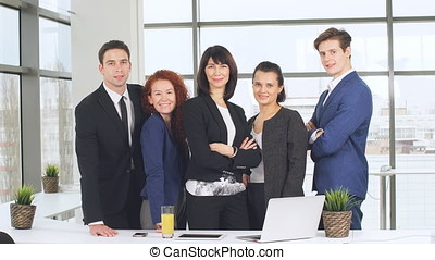 Office and teamwork concept - group of business people having a meeting and showing thumbs up.