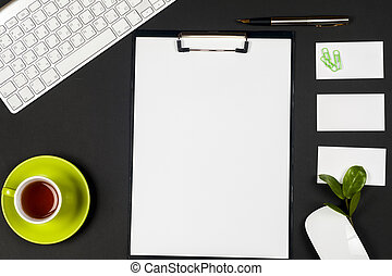 Office black desk table with white computer, business card blank, flower, coffee cup and pen.