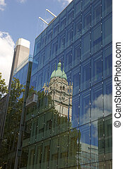 office block - An old tower reflected in athe glass of a...