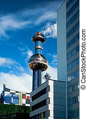 Conventional office building contrasts with chimney and part of waste-to-energy plant in Spittelau, Vienna, Austria. This famous Vienna landmark was designed by architect artist Friedensreich Hundertwasser.