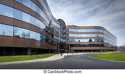 Office building exterior in brick and glass with a blue sky