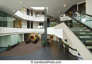 Office building interior lobby with skylight, staircases and balconies