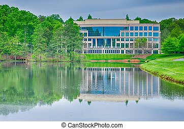office building reflecting in lake
