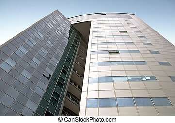 Office building with a hinged facade. Part of the facade opaque aluminum panel, part of - a complete glazing. Against the background of blue sky. Horizontal orientation.