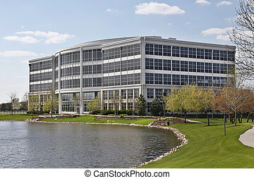 Five story office building with lake in suburbs
