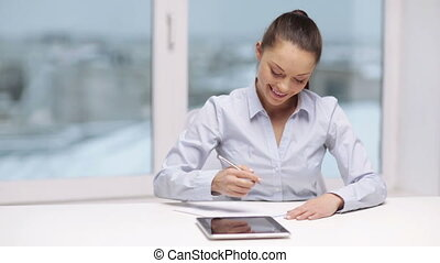 smiling businesswoman with tablet pc in office - office,...