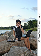 office by the sea: the girl on the rocks with a laptop and a desktop phone