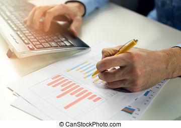 office clerk working with statistical reports and entering...