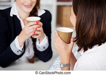 Office coffee break with two female colleagues sittng...