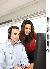 Office couple working at a computer with a headset