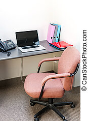 Workstation in office with swivel chair desk and laptop computer
