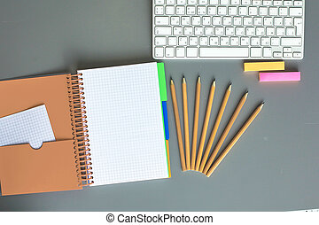 Office desk table with blank notebook, computer, supplies and coffee cup. Top view with copy space