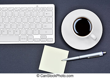 Office desk table with empty notes, coffee cup and keyboard computer