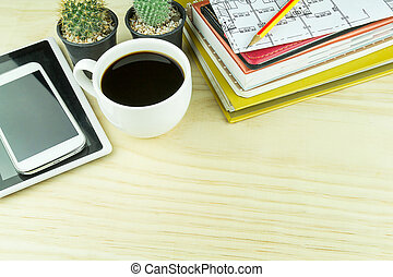 Office desk table with notebook, glasses, smart phone and a cactus