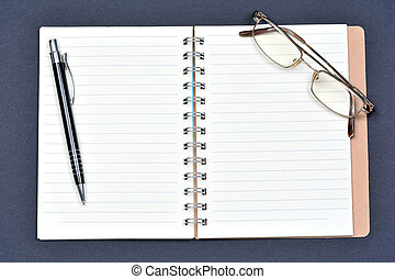 Office desk table with open notebook paper, pen and eyeglasses