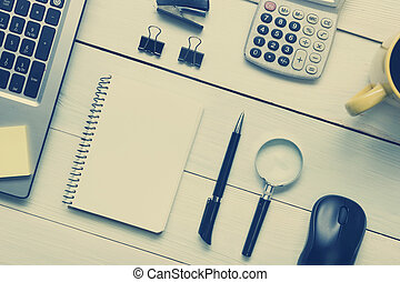 Office desk table with supplies and coffee cup. Top view. Copy space for text. Toned image.