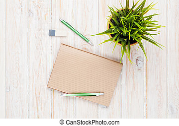 Office desk table with supplies and flower