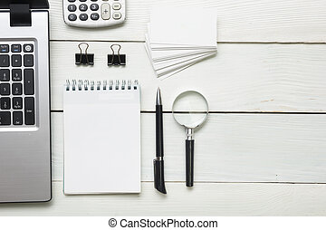 Office desk table with supplies. Top view. Copy space for text. Laptop, blank notepad, pen, magnifying glass, calculator, business card