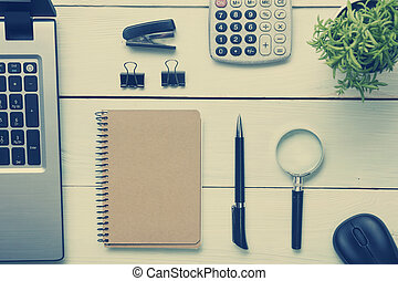Office desk table with supplies. Top view. Copy space for text. Laptop, blank notepad, pen, magnifying glass, calculator, reminder, flower.