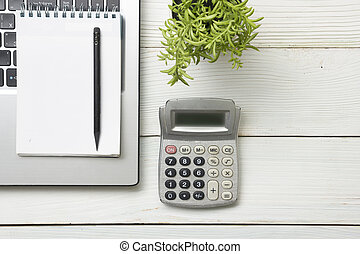 Office desk table with supplies. Top view. Copy space for text. Laptop, notepad, pen, calculator and flower.