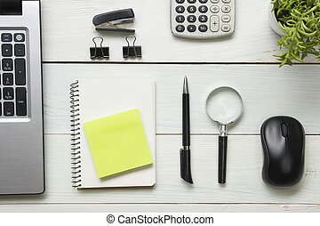 Office desk table with supplies. Top view. Copy space for text. Laptop, notepad, pen, magnifying glass, calculator, remindmer, flower.