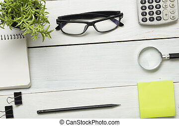 Office desk table with supplies. Top view. Copy space for text. Notepad, pen, glasses, calculator, reminder, flower.