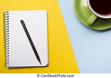 Office desk table with supplies top view. Notepad, pen and colorful paper. Copy space for text