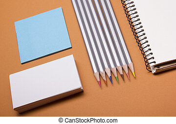 Office desk table with supplies top view. Notepad, pencil and blank business card colorful paper. Copy space for text