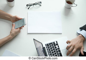 Office desk top view, woman with phone, man on laptop