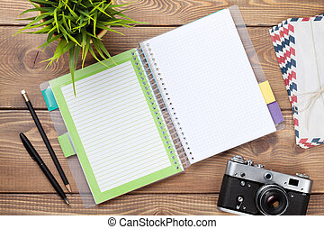 Office desk with calendar notepad, camera, supplies and flower