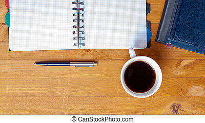 office desk with notebook and blue pen and cup of coffee with copy space. Top view