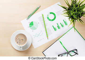 Office desk workplace with charts, coffee cup, plant and notepad on wooden table. Top view.