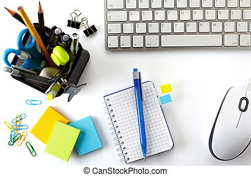 Office desktop with keyboard, mouse, notebook and basket of writing tools