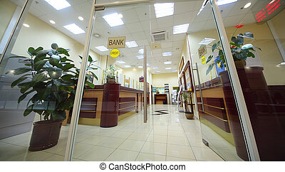 Office entrance area of bank with reception counter; light...