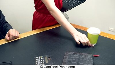 Office flirt. An attractive woman in a red jumpsuit puts her...